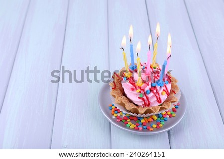 Birthday cup cake with candles on saucer and sparkles on color wooden background - stock photo