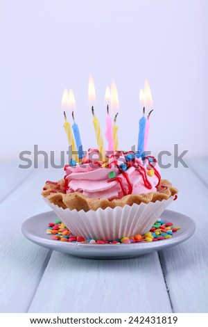 Birthday cup cake with candles on saucer and sparkles on color wooden table and light background - stock photo