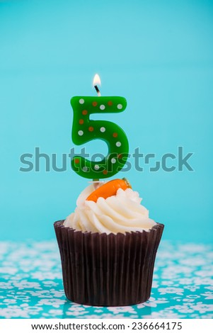 birthday cup cake with number five candle on blue background - stock photo