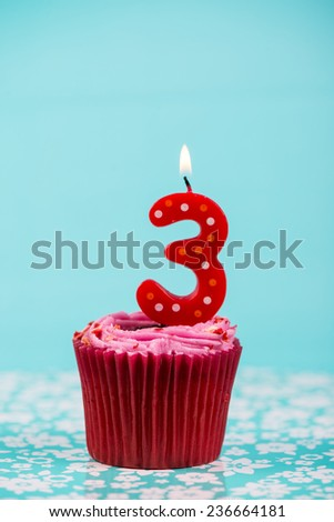 birthday cup cake with number three candle on blue background - stock photo