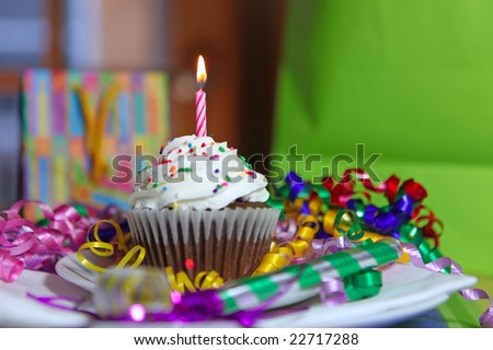Birthday Cup Cake With One Lit Candle and Gifts in the Background - stock photo