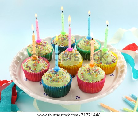 Birthday cup cakes all with their own candles burning. - stock photo