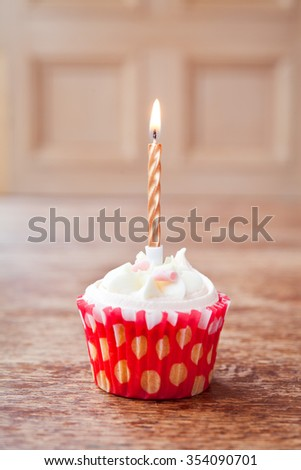 birthday cupcake lit candle on natural wooden bakground