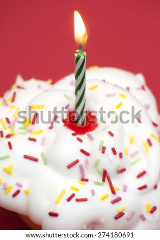 Birthday cupcake over red background