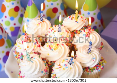 Birthday cupcake plate with lit candles - stock photo
