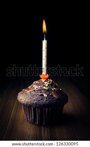 Birthday cupcake with burning candle - low key - stock photo