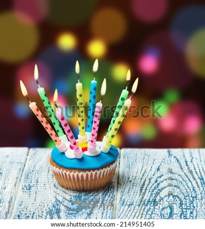Birthday cupcake with burning candles on the color background - stock photo