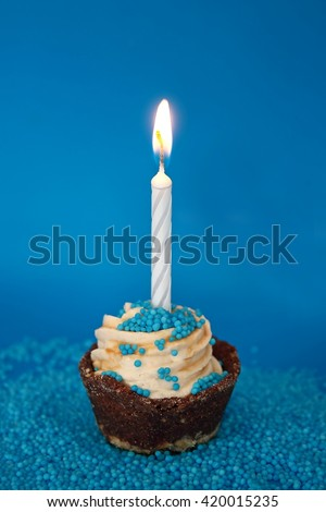 Birthday cupcake with candle, on blue  background  - stock photo