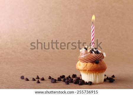 birthday cupcake with candle on chocolate background - stock photo
