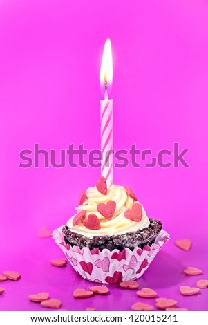 Birthday cupcake with candle, on magenta background  - stock photo