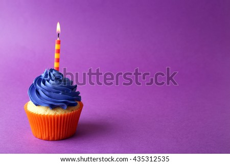 Birthday cupcake with candle on purple background - stock photo