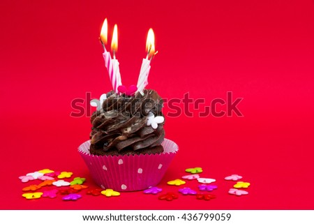 birthday cupcake with candles on red background with colorful decoration - stock photo