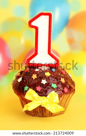 Birthday cupcake with chocolate frosting on bright background - stock photo