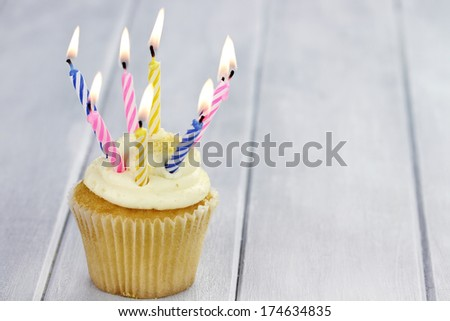 Birthday cupcake with eight burning candles and copy space. Shallow depth of field. - stock photo