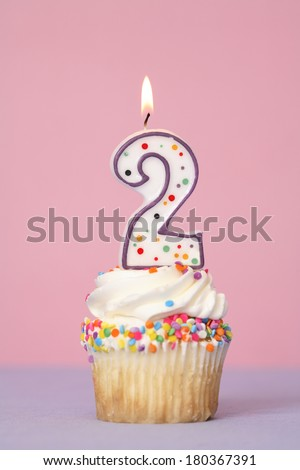 Birthday cupcake with lit candle labeled number 2 on pink and purple background - stock photo