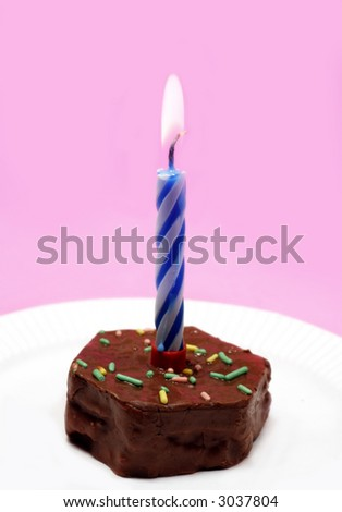 Birthday cupcake with lit candle on pink background
