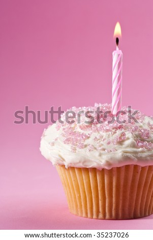 Birthday cupcake with one lit candle and pink sprinkles - stock photo