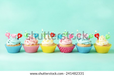 Birthday cupcakes with candles on green background - stock photo