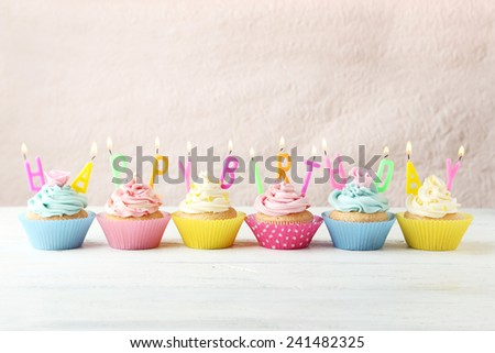 Birthday cupcakes with candles on white wooden background - stock photo