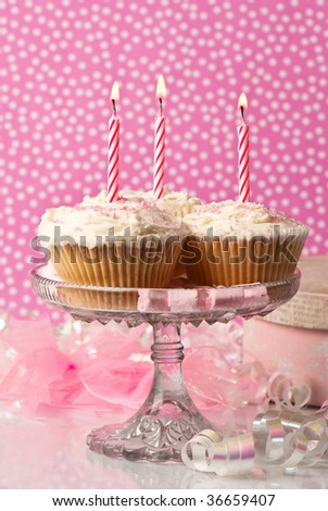 Birthday cupcakes with pink spotty background - stock photo