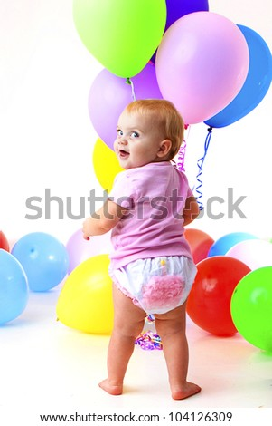 Birthday girl:  adorable baby wearing cupcake bloomer and holding balloons peeks over her shoulder - stock photo