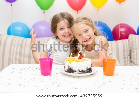 Birthday girl and her friend enjoying birthday party - stock photo
