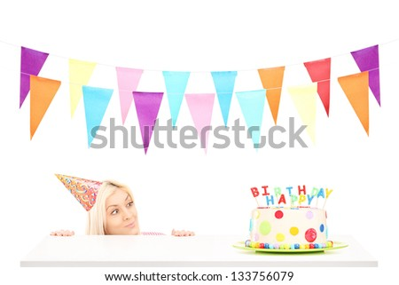Birthday girl with a party hat looking at a birthday cake isolated on white background - stock photo