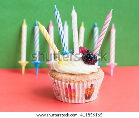 Birthday homemade cupcake with fresh raspberry, blackberry and cream  topping  and candles on colorful background