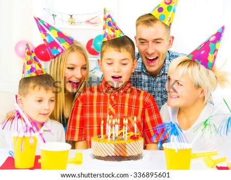 Birthday. Little boy blows out candles on birthday cake at party, Happy big family celebrating birthday of kid - stock photo