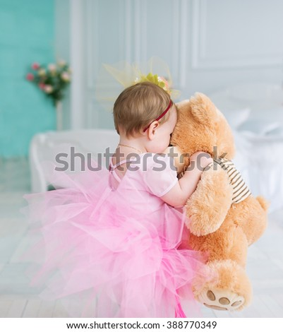 Birthday of the little girl. She has received a gift - a beautiful teddy bear. - stock photo
