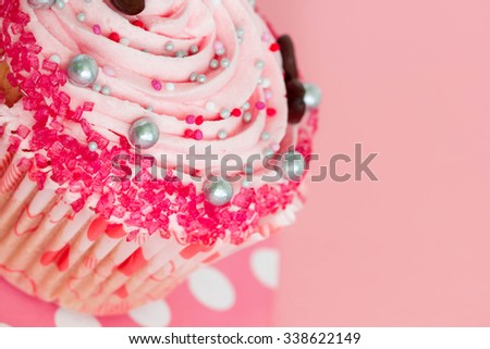 Birthday or wedding cupcake with strawberry icing on pink background. - stock photo
