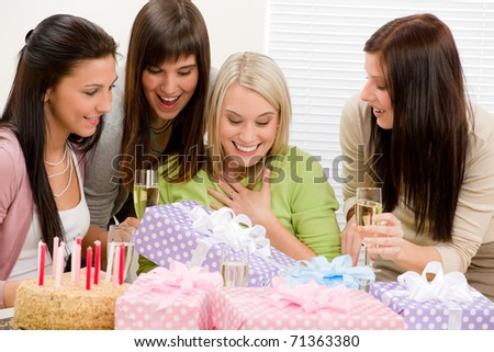 Birthday party - happy woman getting present, champagne, cake - stock photo