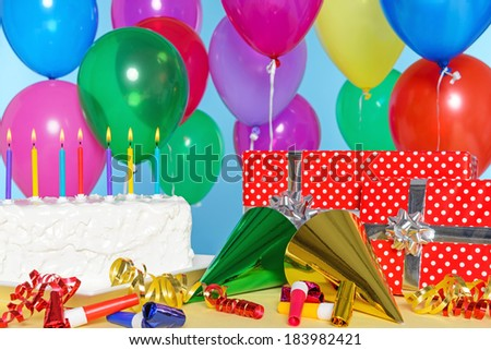 Birthday party still life with cake, balloons, presents, streamers and hats. - stock photo