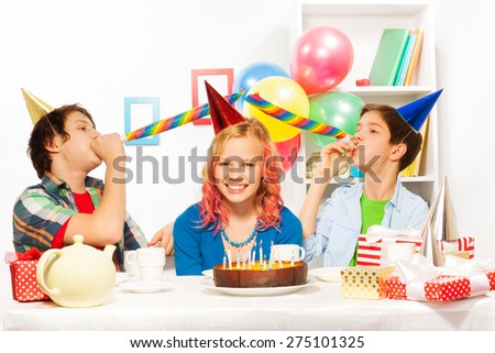 Birthday party with boys blow noisemaker horns - stock photo