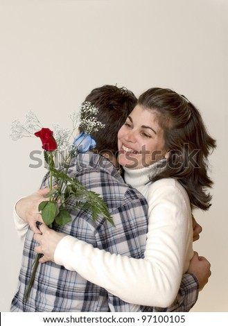 Birthday present and a loving hug. Latin family having quality time together: a small celebration. Hispanic woman happy of getting flowers. - stock photo