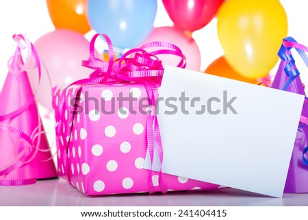 Birthday present and blank card with balloons in background - stock photo