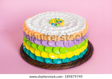 Birthday rainbow cake for kids party on pink background - stock photo