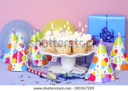 Birthday still life with cupcakes presents, balloons, and party hats - stock photo