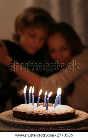 Birthday wishes - Serene siblings sharing a precious moment in front of the lighted candles.  The focus is on the front of the cake. - stock photo