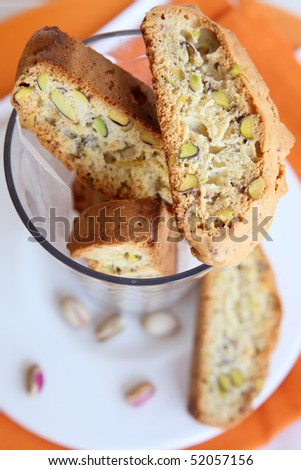 Biscotti with pistachios in a glass beaker on the bright napkins