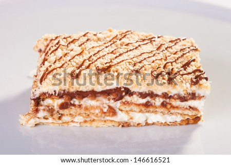 Biscuit cake with vanilla cream and nuts