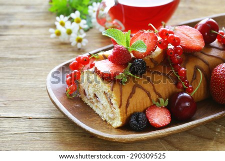 biscuit roulade with butter cream and fresh berries - stock photo