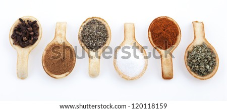 Biscuit spoons with herbs in a row