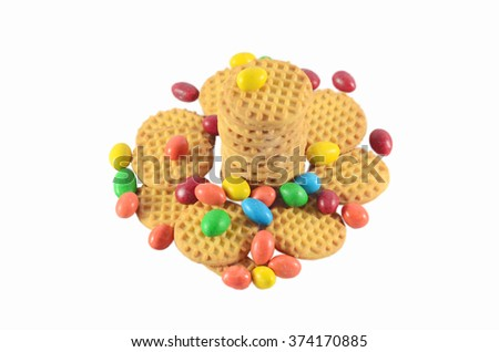 BISCUITS - A stack of delicious round biscuits with colourful chocolates. isolated on white background. - stock photo