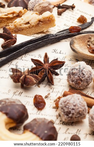 Biscuits and spices lying on a cookbook - stock photo