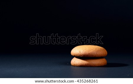 Biscuits filled with chocolate cream. Chocolate cream cookies. brown chocolate biscuits with cream filling on black background. - stock photo