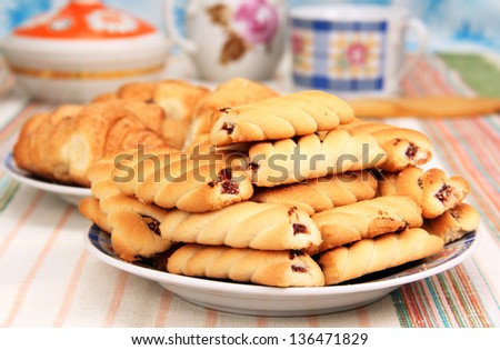 biscuits in a bowl close up in front of a plate of croissants and dining utensils. - stock photo