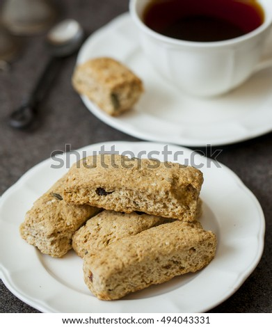 Biscuits on the saucer with cup of tea on bacground