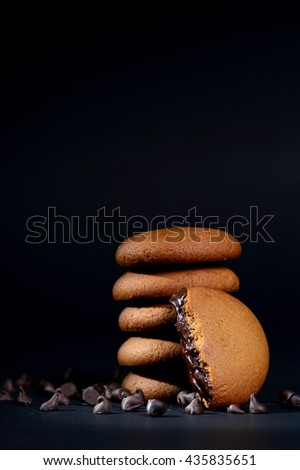 BISCUITS - Stack of delicious cream biscuits, Biscuits filled with chocolate cream. Chocolate cream cookies. brown chocolate biscuits with cream filling on black background. - stock photo