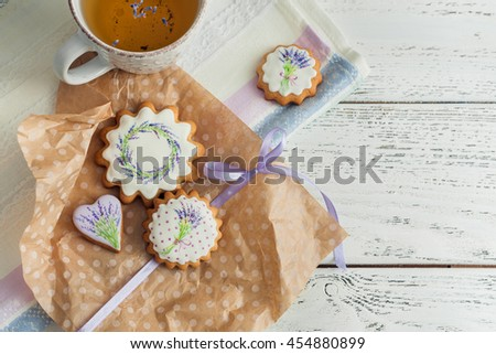 Biscuits vanilla cookies with cup of tea on wooden background. Floral icing decorated cookies.